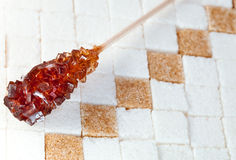 Sugar stick lies on lumpy sugar Royalty Free Stock Photography