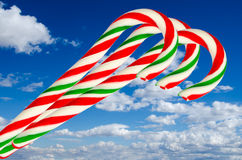 Three sugar sticks in white green and red on background sky and Stock Photos