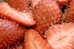 Sugar strawberries. Close up on some sliced strawberries covered in white sugar granules royalty free stock image