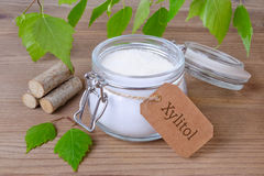Sugar substitute xylitol, a glass jar with birch sugar, liefs and wood. On wooden background royalty free stock images