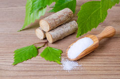 Sugar substitute xylitol, scoop with birch sugar, liefs and wood. Sugar substitute xylitol, a scoop with birch sugar, liefs and wood on wooden background Royalty Free Stock Image