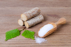 Sugar substitute xylitol, scoop with birch sugar, liefs and wood. Sugar substitute xylitol, a scoop with birch sugar, liefs and wood on wooden background stock photo