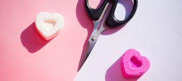 Sugar sweets on different sides and scissors, as a symbol of separation of lovers. On divided background royalty free stock photography