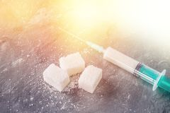 Sugar in a syringe. Conceptual depiction of dependence on the sweet. Sugar is a drug. Injection of sweets. Stock Image