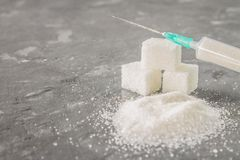Sugar in a syringe. Conceptual depiction of dependence on the sweet. Sugar is a drug. Injection of sweets. Royalty Free Stock Image