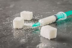 Sugar in a syringe. Conceptual depiction of dependence on the sweet. Sugar is a drug. Injection of sweets. Stock Photography