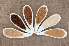 Sugar Types. Selection of demarara, granulated, molasses, muscovado, crystal and light brown sugar in white bowls over hessian background Stock Images
