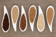 Sugar Types. Sugar varieties in white dishes over hessian background Stock Photos