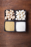 Sugar types. In black bowls over the wooden background royalty free stock photos