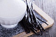 Sugar and vanilla beans. Sugar in a bowl and whole vanilla beans Royalty Free Stock Photography