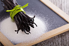 Sugar and vanilla beans. Sugar on a chalkboard and whole vanilla beans Stock Photography