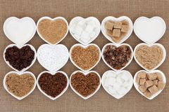 Sugar Varieties. Brown and white sugar selection in heart shaped bowls over hessian background Royalty Free Stock Photo