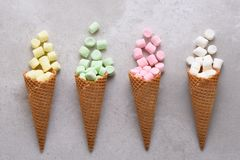 Sugar Waffle Ice Cream Cones filled with colorful marshmallows spilling onto tile table royalty free stock image