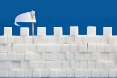 Sugar Wall. A castle wall made of sugar cubes with a white flag of truce Stock Photo