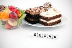 Sugar word on dices. Cake and fruits in background royalty free stock photos