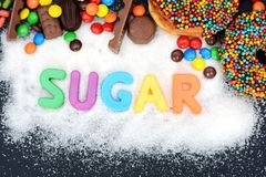 Sugar word written on white sugar background with lot of multicolored sweets. Sugar word written with plastic letters on white sugar background with lot of Royalty Free Stock Photos