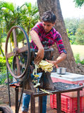 Sugarcane juice extracter. Image showing a adolescent boy extracting sugarcane juice in machine at a roadside stall in india. Image can be used  to show the Royalty Free Stock Images