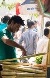 Sugarcane juice vendor pouring juice Royalty Free Stock Photos