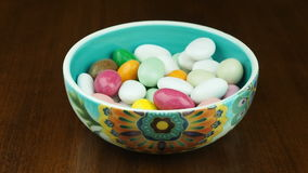Sugared almonds dropping empty bowl stock video footage