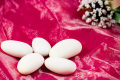 Sugared almonds. Five white sugared almonds on pink background stock photos
