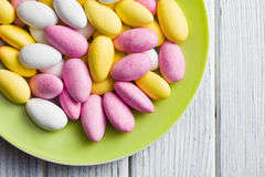 Sugared almonds on green plate Royalty Free Stock Image