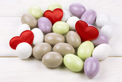 Sugared almonds with red heart shaped confetti Stock Photography