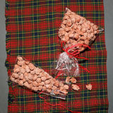 Sugared Almonds. Wrapped in plastic bags with red bows. Checkered background, top view royalty free stock image