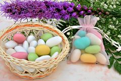 Sugared colors. In a basket with flowers in the background Stock Photography