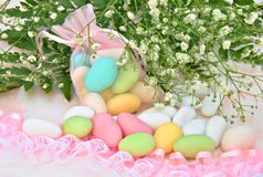 Sugared colors. In a basket with flowers in the background royalty free stock images