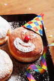 Sugared Donuts with Clown Face and Carnival Props. Close up Delicious Sugared Donuts on Tray with Clown Face and Carnival Props on Top of Wooden Table stock image