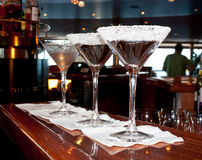 Sugared Martini Drink Glasses At Bar. A row of glasses with sugared rims stand at the bar waiting for some fun royalty free stock image
