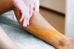 Sugaring Sugar waxing feet in the beauty salon stock photo