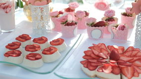 Sugary appetizers and strawberries on white table outdoor. stock video