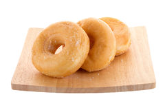 Sugary donut on a wooden plate isolated on a white background.  Stock Images