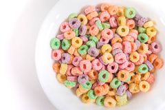 Fruity cereal in a bowl. Sugary and fruity cereal with different colors in a bowl with white  background Royalty Free Stock Images