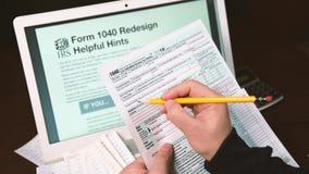 1040 suggerimenti utili della riprogettazione su un monitor del computer portatile, forma di esame della mano dell'uomo 1040 stock footage