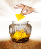Suggestion. A hand depositing a blank paper into a suggestion jar Stock Photos