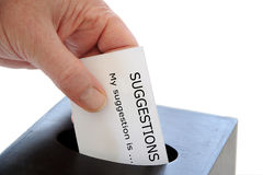 Suggestion Box. Close-up of a slip being placed in a suggestion box over a white background royalty free stock photos