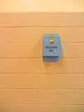 Suggestion box on wall. A blue suggestion box with a lock on an orange wall Royalty Free Stock Images