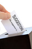 Suggestions. Close-up of a slip being placed in a suggestion box over a white background royalty free stock photography