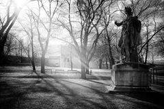 Autumn view of Prague, Vyšehrad gardens, with sunbeams shining through the bare branches of trees and n old statue. Suggestive autumn view of the gardens in stock photo
