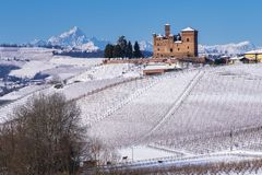 Suggestive view of the Castle of Grinzane Cavour on the snowy hills and vineyards stock photo