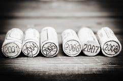Sugheri datati della bottiglia di vino sui precedenti di legno Fotografia Stock