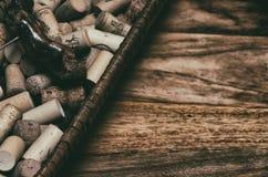 sugheri del vino in un vecchio pane del canestro sul legname del palissandro Fotografia Stock Libera da Diritti
