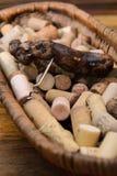 sugheri del vino in un vecchio pane del canestro sul legname del palissandro Immagine Stock Libera da Diritti