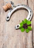 Sughero del ferro di cavallo, dell'acetosella e del champagne su vecchio di legno Fotografie Stock Libere da Diritti
