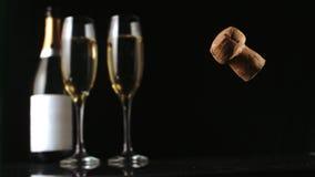 Sughero di Champagne che cade davanti a due flauto e bottiglie di vetro stock footage