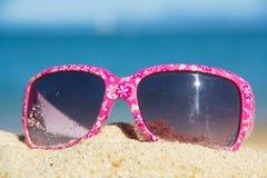 Suglasses rosa sulla sabbia Fotografia Stock