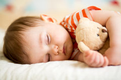 Säuglingsbaby, das mit Plüschspielzeug schläft Stockbild