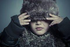 Säuglingskind mit Pelzhut und Winter beschichten, kaltes Konzept und stor Lizenzfreie Stockfotos